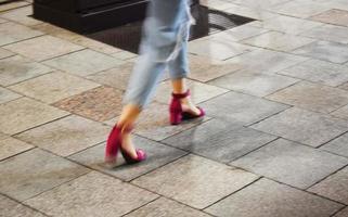 Mujer caminando vistiendo pantalones vaqueros azules y un par de sandalias rosas foto