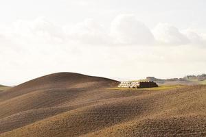Fardos de heno y tierras agrícolas labradas durante el día en Italia foto