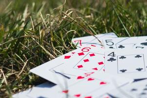 Playing cards in green grass close up photo
