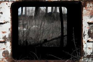 Window of old rusty carriage in dry gras photo