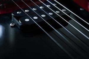 Primer plano de la guitarra eléctrica roja sobre fondo negro foto