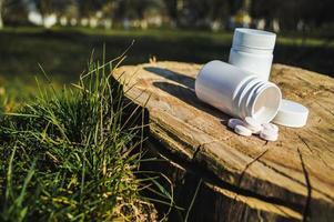White jar and white pills lie on a stump photo