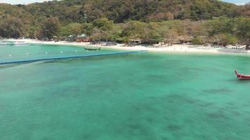 Idyllic Banana Beach Bay with floating dock platform and rural fishing boats moored on the emerald waters in Koh Hey, Coral Island, Thailand - Aerial ground level Fly-backwards shot video