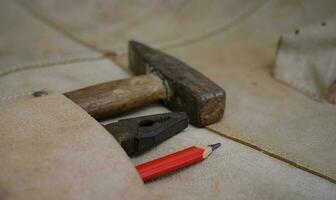 Colección de herramientas de mano antiguas para trabajar la madera en el delantal de cuero sobre un banco de trabajo de madera rugosa foto