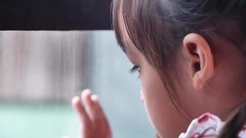 Sad asian little girl looking out the window in the rainy day video