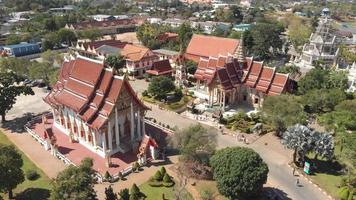 Fly-over survey view of Chalong Temple grounds and shrines in Phuket, Thailand - Aerial Fly-over low angle panoramic shot video