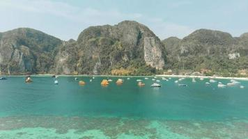 Tonsai Bay unspoilt exotic paradise harboring fleet of small boats in Ko Phi Phi Don Island, Thailand - Aerial Fly-over shot video