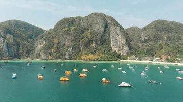 Picturesque scenic view of large bay crowded with moored boats in Ko Phi Phi Don Island Paradise in Thailand - Aerial Fly-over panoramic shot video