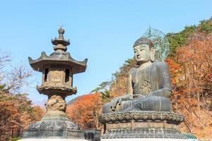 La tradicional estatua de Buda y coloridos árboles en el templo shinheungsa en el parque nacional de Seoraksan en otoño de Corea del Sur foto