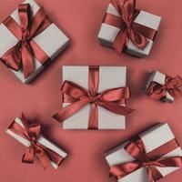 Cajas de regalo envueltas en papel artesanal con cintas marrones y lazos planos monocromáticos festivos foto