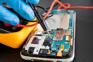 Técnico que repara el interior del teléfono móvil mediante un circuito integrado de soldador el concepto de tecnología de hardware de datos foto