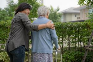 Ayude y cuide a la anciana asiática mayor o anciana que use un andador con una salud fuerte mientras camina en el parque en felices vacaciones frescas foto