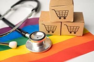 estetoscopio negro en la bandera del arco iris con caja de compras en línea símbolo del mes del orgullo lgbt celebrar anual en junio símbolo social de gay lesbianas bisexual transgénero derechos humanos y paz foto