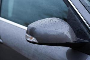 Rear view mirror of car wet from drops of water photo