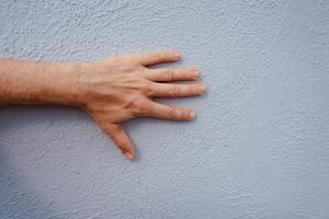mano gesticulando en la pared azul foto
