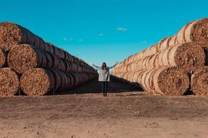 A girl in a gray coat stands in a field near a larger bale with hay photo