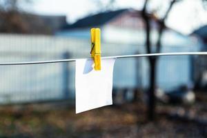 una hoja de papel blanca sujeta con una pinza de ropa amarilla foto