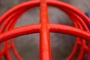 Tubos rojos en el patio de recreo de cerca en gotas de lluvia foto