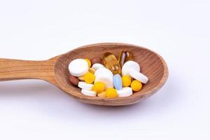 Pastillas de medicina y drogas en cuchara de madera sobre fondo blanco con espacio de copia foto