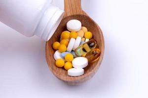 Pastillas de medicina y drogas en una cuchara de madera sobre fondo blanco con espacio de copia foto