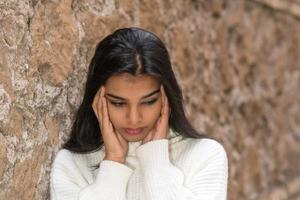 Close Up retrato de una mujer morena frotando sus sienes para aliviar un terrible dolor de cabeza foto