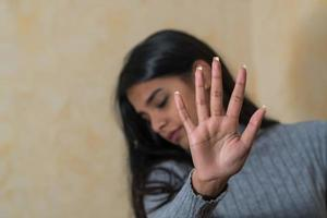 Self defence young Indian woman covering her face with hand Woman says stop photo