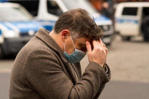 A man wearing a medical protective mask with his hands on his head due to receiving bad news or a headache photo