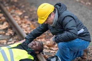 African American railroad engineer injured in an accident at work on the railway tracks his coworker helping him photo