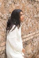 Retrato de una joven morena contemplativa apoyada contra una pared de ladrillos foto