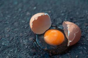 Broken egg on asphalt as a symbol of failure photo