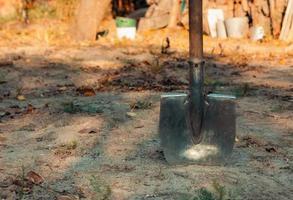 Close-up of shovel head dug into sand photo