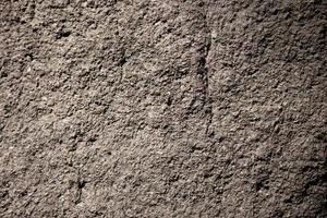 Fondo de textura de roca o piedra natural gris escabrosa foto