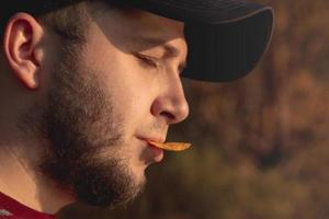 Bearded man in the forest eating chips photo