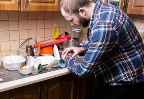 A young bearded guy looks at his watch and is shocked by the amount of dirty dishes lying in the kitchen sink photo
