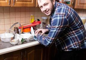 A young bearded guy looks at his watch and is happy by the amount of dirty dishes lying in the kitchen sink photo