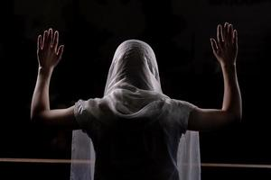 Silhouette of a young girl who sits in church and praying with hands raised up photo