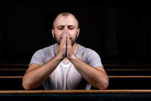 A Christian man in white shirt is sitting and praying with humble heart in the church photo