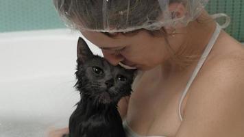 Eine Frau badet eine Katze im Badezimmer video