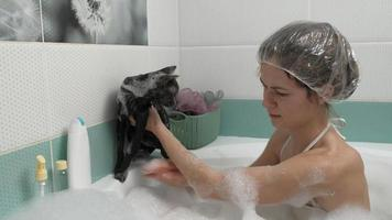 A woman bathes a cat in the bathroom video