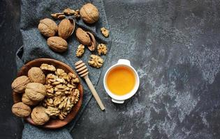 Walnut in wooden bowl on wooden background with copy space photo