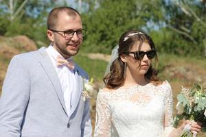 Fotografía de boda novios de moda en gafas de sol en la naturaleza foto