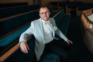 Foto de boda de las emociones de un novio barbudo con gafas en una chaqueta gris en el edificio de la iglesia