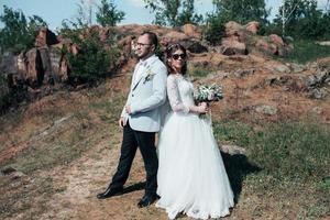 Fotografía de bodas novios de moda en gafas de sol en la naturaleza en las rocas foto