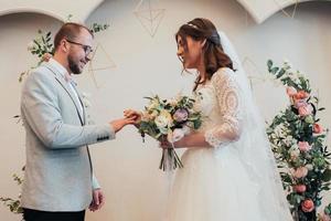 Bride and groom exchange wedding gold rings photo