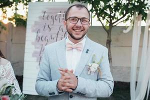 foto de boda de las emociones de un novio barbudo con gafas en una chaqueta gris y estilo rústico