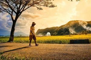 An old man walking holding fishing rod at dusk time photo