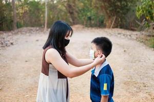 The mother is wearing a mask to protect her son from the covid19 virus photo