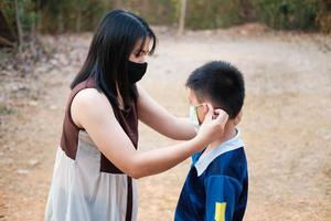 The mother is wearing a mask to protect her son from the covid virus photo