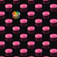 Patrón de macarons rosados con una reflexión sobre un fondo negro foto