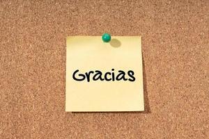Gracias - palabra de agradecimiento en idioma español en nota amarilla en tablero de corcho foto